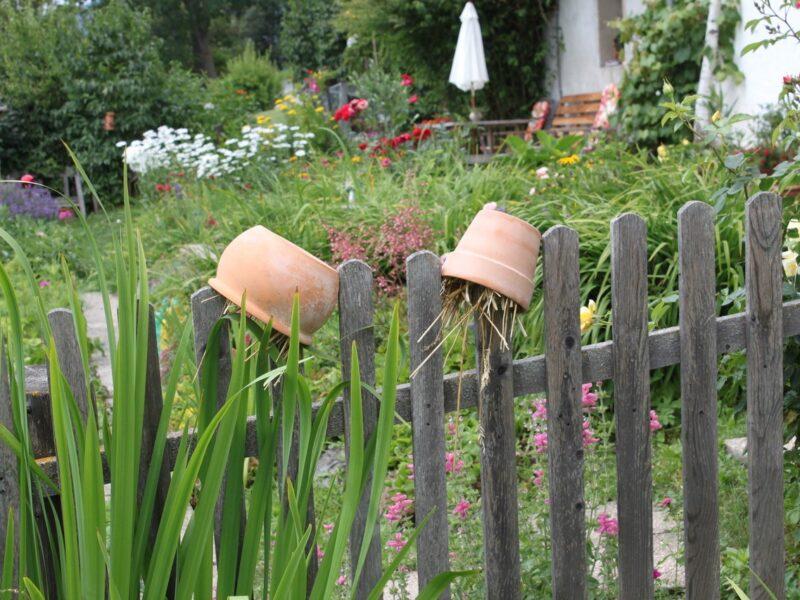 Zaun im Garten mit Blumentopfen